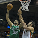 Milwaukee Bucks' Eaza Pachulia tries to block the shot of Boston Celtics' Vitor Faverani during the first half of an NBA basketball game Saturday, Nov. 30, 2013, in Milwaukee The Associated Press