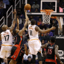 Phoenix Suns' Markieff Morris (11) tips in a basket between Toronto Raptors' Kyle Lowry (7) and Amir Johnson (15) as Suns' P.J. Tucker (17) looks to rebound during the second half of an NBA basketball game on Friday, Dec. 6, 2013, in Phoenix The Associate