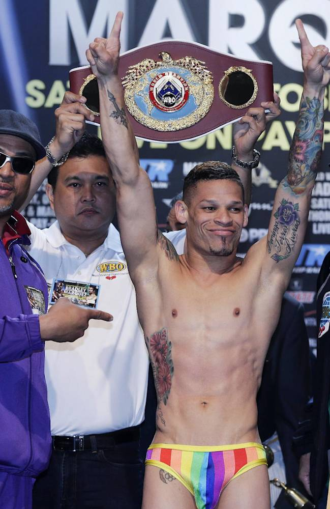 Orlando Cruz poses for photos while standing on the scale during the weigh-in for the WBO featherweight title fight against Orlando Salido, Friday, Oct. 11, 2013, in Las Vegas. Cruz, boxing's first openly gay fighter, will take on Salido in the 12-round title fight on Saturday