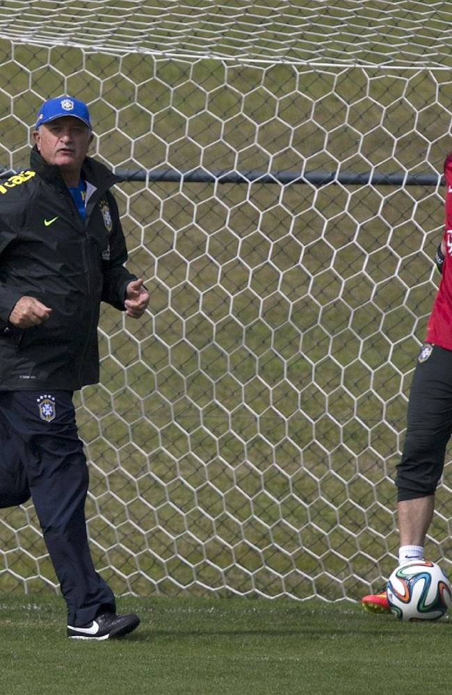 Brazil's coach Luiz Felipe Scolari runs next to goalkeeper Julio Cesar during a practice session at the Granja Comary training center, in Teresopolis, Brazil, Monday, July 7, 2014. Brazil will face Germany on Tuesday in a World Cup semifinal match without Neymar