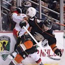 Anaheim Ducks' Andrew Cogliano, front, body checks Calgary Flames' Mark Giordano during an NHL hockey game Tuesday, Nov. 25, 2014, in Anaheim, Calif The Associated Press