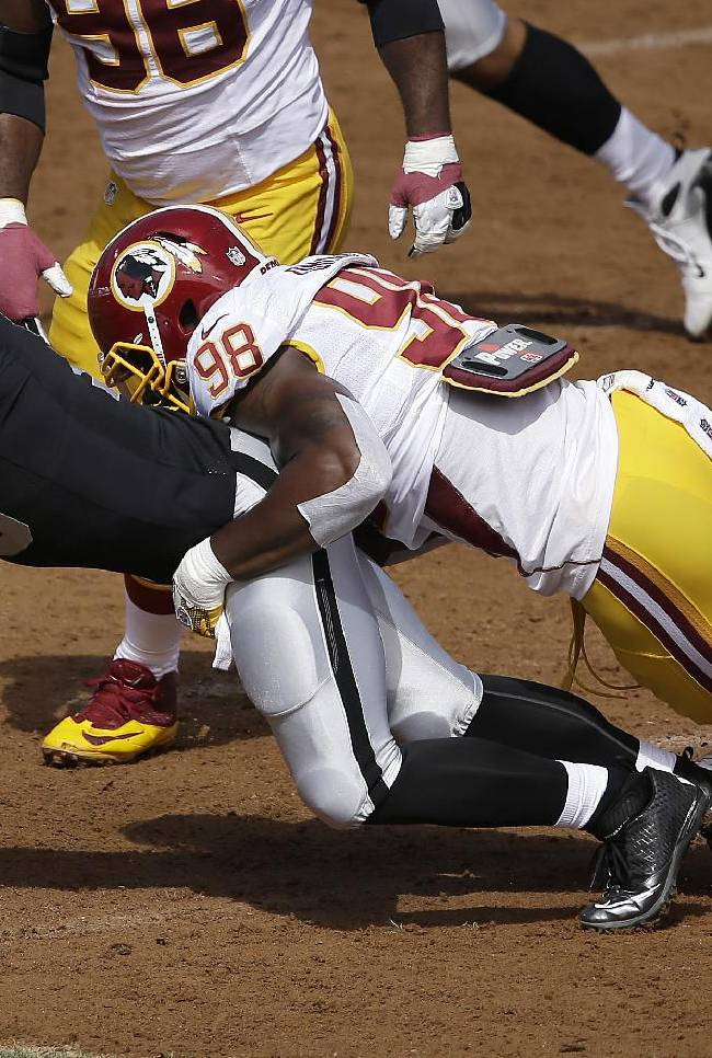 Washington Redskins outside linebacker Brian Orakpo (98) sacks Oakland Raiders quarterback Matt Flynn (15) during the first quarter of an NFL football game in Oakland, Calif., Sunday, Sept. 29, 2013