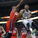 Boston Celtics guard Phil Pressey (26) passes the ball against the defense of Washington Wizards center Kevin Seraphin (13) during the second half of an NBA basketball game in Boston, Wednesday, April 16, 2014 The Associated Press