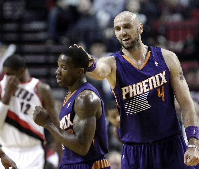 Phoenix Suns center Marcin Gortat, right, pats teammate Eric Bledsoe on the head after Bledsoe fed him the pass for a score during the second half of an NBA preseason basketball game against the Portland Trail Blazers in Portland, Ore., Wednesday, Oct. 9, 2013.  Gortat scored eight points as the Suns won 104-98