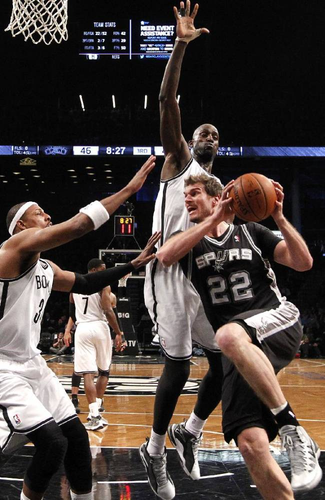 San Antonio Spurs' Tiago Splitter (22), of Brazil, looks to pass against Brooklyn Nets' Paul Pierce, left, and Kevin Garnett during the second half of an NBA basketball game on Thursday, Feb. 6, 2014, in New York. Brooklyn won 103-89