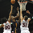 New Orleans Pelicans' Tyreke Evans, center, shoots over Atlanta Hawks' Cartier Martin (20) and Mike Muscala (31) in the first half of an NBA basketball game Friday, March 21, 2014, in Atlanta The Associated Press