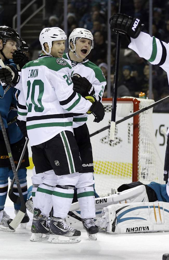 Dallas Stars' Antoine Roussel, center, of France, celebrates his goal with teammates Cody Eakin (20) and Alex Goligoski (33) during the second period of an NHL hockey game against the San Jose Sharks on Saturday, Dec. 21, 2013, in San Jose, Calif