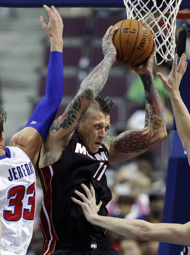 Miami Heat forward Chris Anderson (11) tries to pass the ball against Detroit Pistons forwards Jonas Jerebko (33) and Kyle Singler, right, in the first half of an NBA basketball preseason game on Thursday, Oct. 10, 2013, in Detroit
