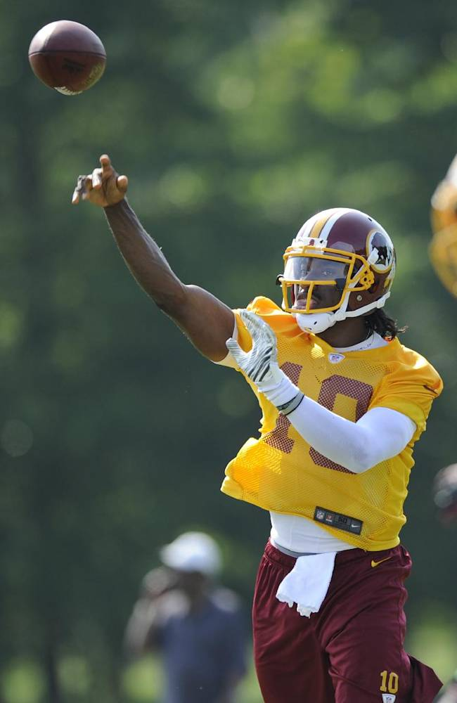 Washington Redskins quarterback Robert Griffin III (10) throws a pass during NFL football minicamp, Tuesday, June 17, 2014, in Ashburn, Va