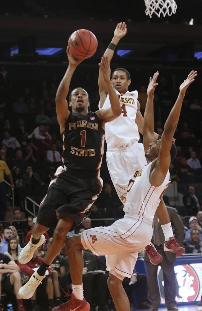 Florida State's Devon Bookert (1) drives past Minnesota's Deandre Mathieu (4) and another defender during the second half of an NCAA college basketball game in the semifinals of the NIT on Tuesday, April 1, 2014, in New York. Minnesota won 67-64