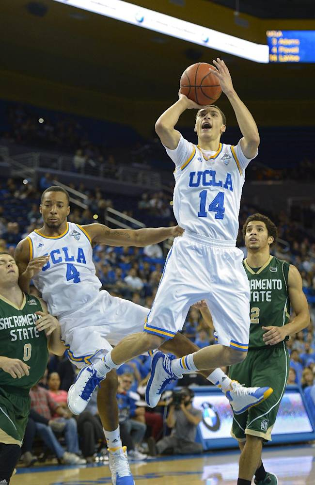 UCLA guard Zach LaVine, second from right, puts up a shot as guard Norman Powell, second from left, falls into Sacramento guard Case Rada, left, while guard Cody Demps looks on during the second half of an NCAA college basketball game, Monday, Nov. 18, 2013, in Los Angeles