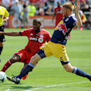 Toronto FC's Jeremy Hall, left, fights for the ball against New York Red Bulls' Markus Holgersson (5) during the fist half of an MLS soccer game Saturday, July 20, 2013, in Toronto. (AP Photo/The Canadian Press, Jon Blacker)