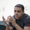 FILE - In this Oct. 3, 2014, file photo, Miami NCAA college basketball guard Angel Rodriguez gestures as he speaks with members of the media before the team's official first practice in Coral Gables, Fla. Rodriguez says he no longer gets recognized in the grocery store, as he did when he was at Kansas State, but the transfer is happy with his new role as a point guard and leader for the Miami Hurricanes. (AP Photo/Wilfredo Lee, File)