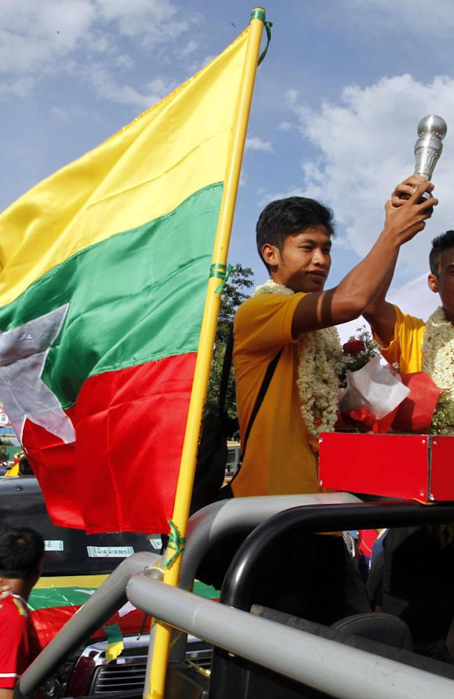 In this photo taken on Aug 24, 2014, Aung Thu, left on vehicle, and Nanda Kyaw, right on vehicle, players of Myanmar U-19 soccer team, waves the trophy as they are welcomed by Myanmar soccer fans upon their arrival after they won 5th edition Hassanal Bolkiah Throphy, in Yangon, Myanmar. The U-19 Myanmar soccer team beat their Vietnamese counterpart 4-3 in the final at the Hassanal Bolkiah National Stadium in Brunei on Saturday