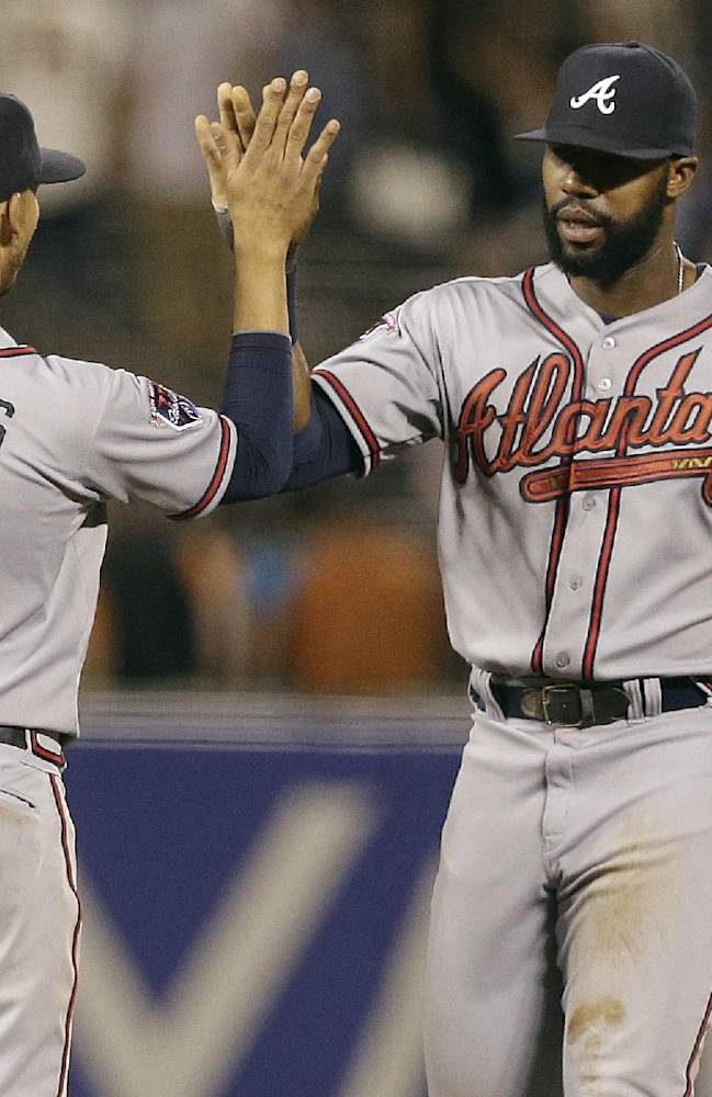 Atlanta Braves shortstop Andrelton Simmons (19) and right fielder Jason Heyward celebrate after the Braves beat the San Francisco Giants in a baseball game in San Francisco, Tuesday, May 13, 2014. The Braves won 5-0. (AP Photo)