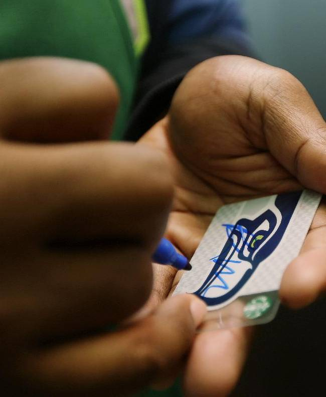 Seattle Seahawks NFL football defensive tackle Brandon Mebane autographs a special Seahawks Starbucks card on Wednesday, Oct. 23, 2013, in Seattle. The Seahawks began a one-week fund-raising campaign Wednesday with Starbucks to benefit Seahawks head coach Pete Carroll's A Better Seattle program, which seeks to reach at-risk youth and prevent gang violence