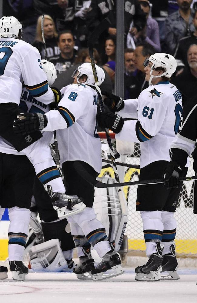 Members of the San Jose Sharks, left, celebrate a game-winning goal by center Patrick Marleau as Los Angeles Kings center Tyler Toffoli, right, looks on during the overtime period in Game 3 of an NHL hockey first-round playoff series, Tuesday, April 22, 2014, in Los Angeles. The Sharks won 4-3