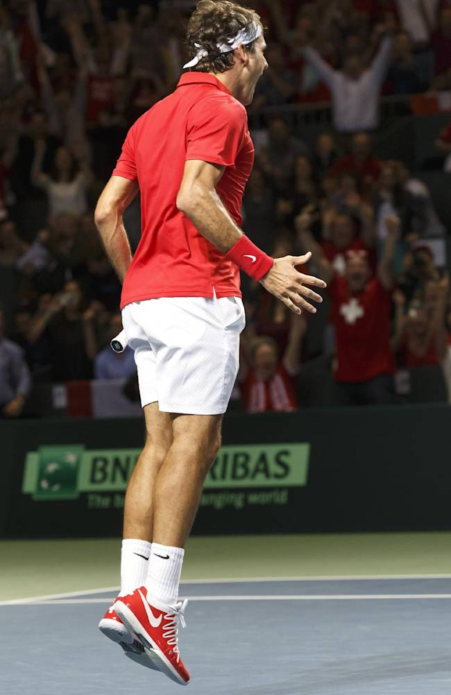 Switzerland's Roger Federer, celebrates after winning the match against Andrey Golubev, of Kazakhstan, during the fourth tennis single match of the Davis Cup World Group Quarterfinal match between Switzerland and Kazakhstan, at Palexpo, in Geneva, Switzerland, Sunday, April 6, 2014.  Roger Federer won the decisive singles match on Sunday to give Switzerland a 3-2 win over Kazakhstan in the Davis Cup and a spot in the semifinals for the first time in 11 years. (AP Photo / Keystone, Salvatore Di Nolfi)