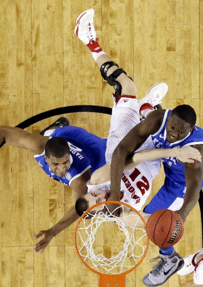Wisconsin guard Traevon Jackson (12) is caught between Kentucky guard Aaron Harrison (2) and forward Julius Randle (30) during the first half of the NCAA Final Four tournament college basketball semifinal game Saturday, April 5, 2014, in Arlington, Texas