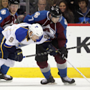 St. Louis Blues left wing Jaden Schwartz (9) lunges for the puck against Colorado Avalanche center John Mitchell (7) as Avalanche left wing Gabriel Landeskog (92) backs up the play during the second period of an NHL hockey game in Denver, Wednesday, Nov.