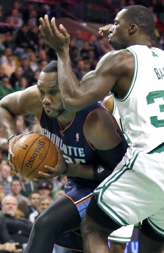 Charlotte Bobcats center Al Jefferson, left, drives to the hoop against Boston Celtics power forward Brandon Bass in the second half of an NBA basketball game in Boston, Wednesday, Nov. 13, 2013. The Bobcats won 89-83