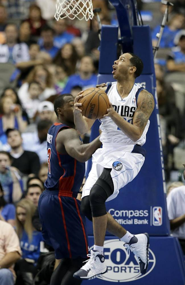Dallas Mavericks guard Devin Harris (20) goes up for a reverse layup over Detroit Pistons' Rodney Stuckey (3) in the first half of an NBA basketball game, Sunday, Jan. 26, 2014, in Dallas