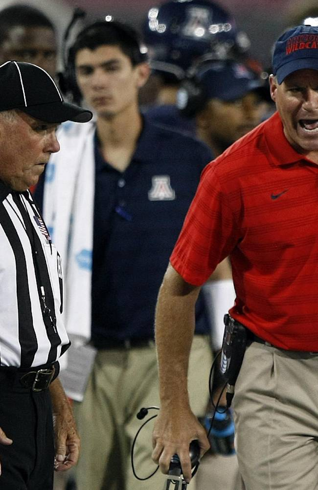 Arizona head coach Rich Rodriguez talks with side judge Dave Cushman during the second half of an NCAA college football game, Friday, Aug. 29, 2014, in Tucson, Ariz