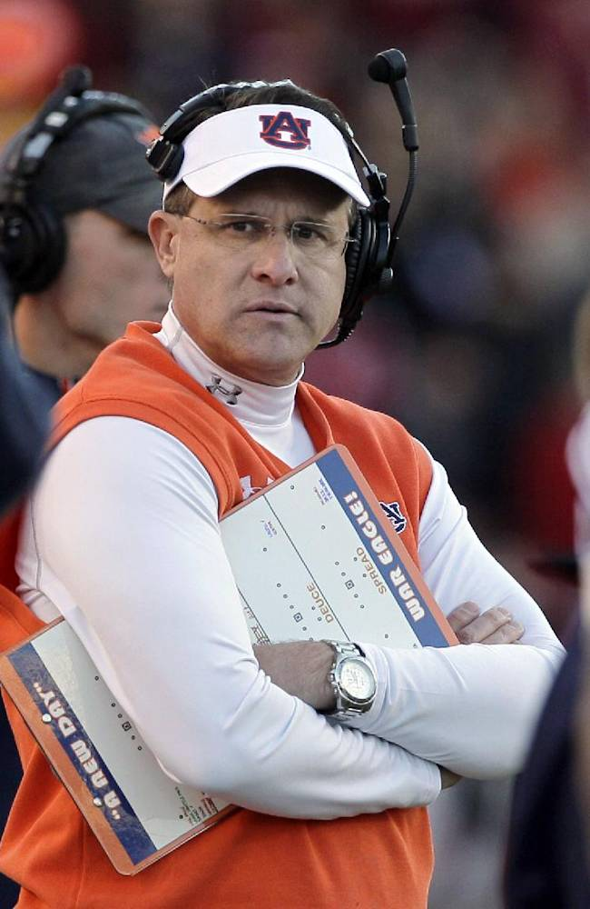 In this Nov. 2, 2013, file photo, Auburn coach Gus Malzahn, center, watches the first half of an NCAA college football game against Arkansas in Fayetteville, Ark. Malzahn led the second-ranked Tigers' transformation into Southeastern Conference champions and has them in the national championship game Jan. 6 against No. 1 Florida State. Malzahn's quick work made him The Associated Press national coach of the year