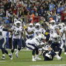 San Diego Chargers players celebrate after nose tackle Sean Lissemore, on ground, recovered a fumble by San Francisco 49ers wide receiver Quinton Patton during overtime in an NFL football game in Santa Clara, Calif., Saturday, Dec. 20, 2014. The Chargers won 38-35. (AP Photo/Ben Margot)