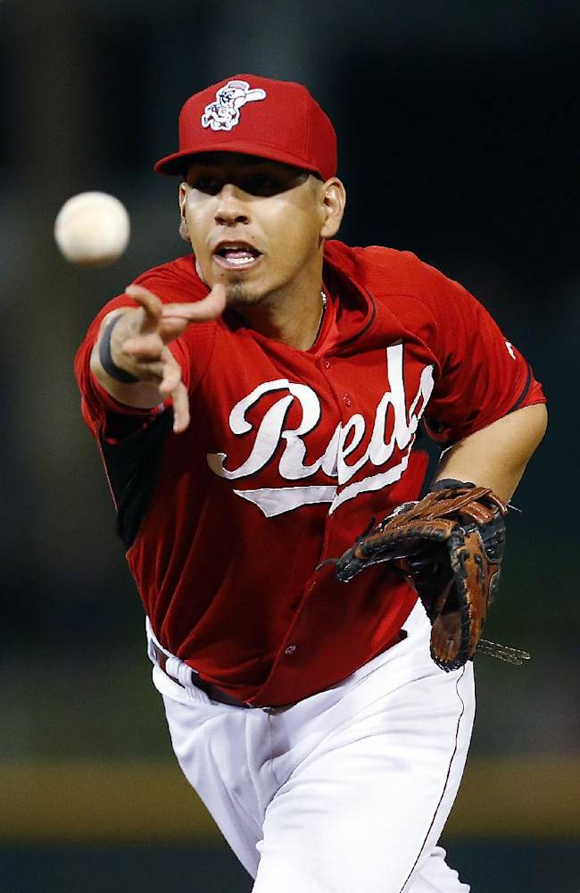 Cincinnati Reds first baseman Neftali Soto tosses the ball to first base against the Los Angeles Dodgers for an out in the eighth inning during an exhibition baseball game in Goodyear, Ariz., Wednesday, March 5, 2014