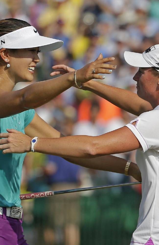 In this June 22, 2014, file photo, Michelle Wie, left, is embraced by runner-up Stacy Lewis after winning the U.S. Women's Open golf tournament in Pinehurst, N.C.  One is tall and powerful, the other compact and precise. Wie and Lewis, for all their differences, have become fast friends in golf. They're also leading an American revival, which resumes this week at Royal Birkdale