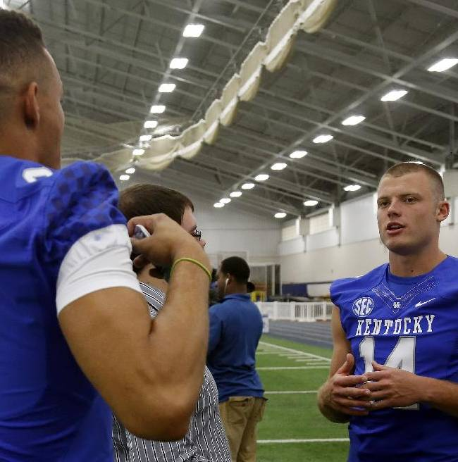 Kentucky's Patrick Towles, right, is interviewed as teammate Blake Bone (6) tries to distract him during the team's NCAA college football media day, Friday, Aug. 8, 2014, in Lexington, Ky