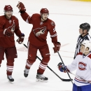 Phoenix Coyotes' Shane Doan (19) celebrates his goal with teammate Oliver Ekman-Larsson (23), of Sweden, as Montreal Canadiens' Ryan White (53) skates past in front of linesman Lonnie Cameron during the third period of an NHL hockey game, Thursday, March