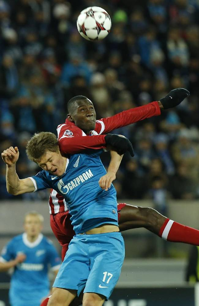 Zenit's Oleg Shatov, left, and Atletico's Joshua Guilavogui struggle for the ball during the Champions League group G soccer match between Zenit and Atletico Madrid at Petrovsky stadium in St.Petersburg, Russia, on Tuesday, Nov. 26, 2013