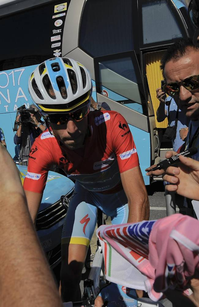 Vincenzo Nibali of Italy, overall leader of the Spanish La Vuelta , crosses alongside supporters before the start of the 19th stage of the  race, a 181-kilometer (112.5-mile) leg between San Vicente de La Barquera and Oviedo, in San Vicente de La Barquera, northern Spain, Friday, Sept. 13, 2013