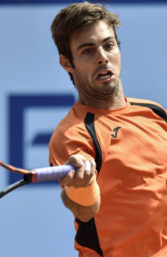 Marcel Granollers of Spain returns a ball to Pablo Andujar of Spain during the quarterfinal match at the Swiss  Open tennis tournament in Gstaad, Switzerland, Friday, July 25, 2014