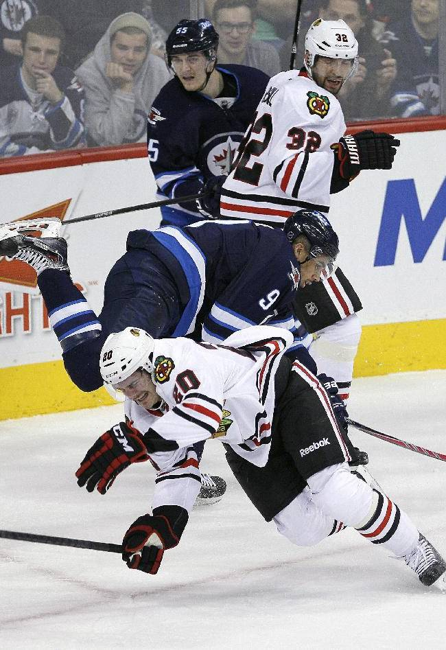 Winnipeg Jets' Evander Kane (9) and Chicago Blackhawks' Brandon Saad (20) collide as Jets' Mark Scheifele, back, and Blackhawks' Michal Rozsival (32) stand by during the first period of an NHL hockey game in Winnipeg, Manitoba on Thursday, Nov. 21, 2013