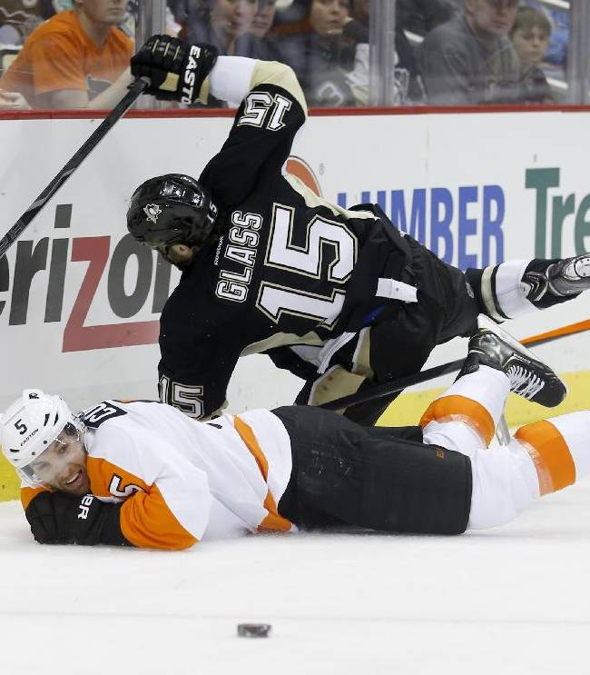The pucks slides away as Pittsburgh Penguins' Tanner Glass (15) and Philadelphia Flyers' Braydon Coburn (5) slide into the boards during the second period of an NHL hockey game on Sunday, March 16, 2014, in Pittsburgh