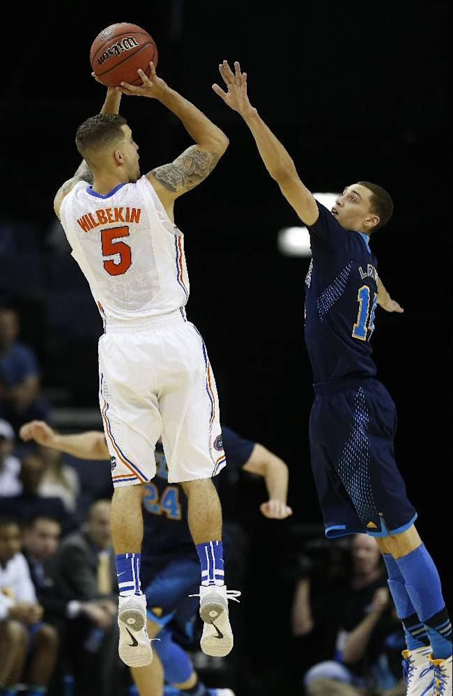Florida guard Scottie Wilbekin (5) shoots a three-point shot over UCLA guard Zach LaVine (14) during the first half in a regional semifinal game at the NCAA college basketball tournament, Thursday, March 27, 2014, in Memphis, Tenn