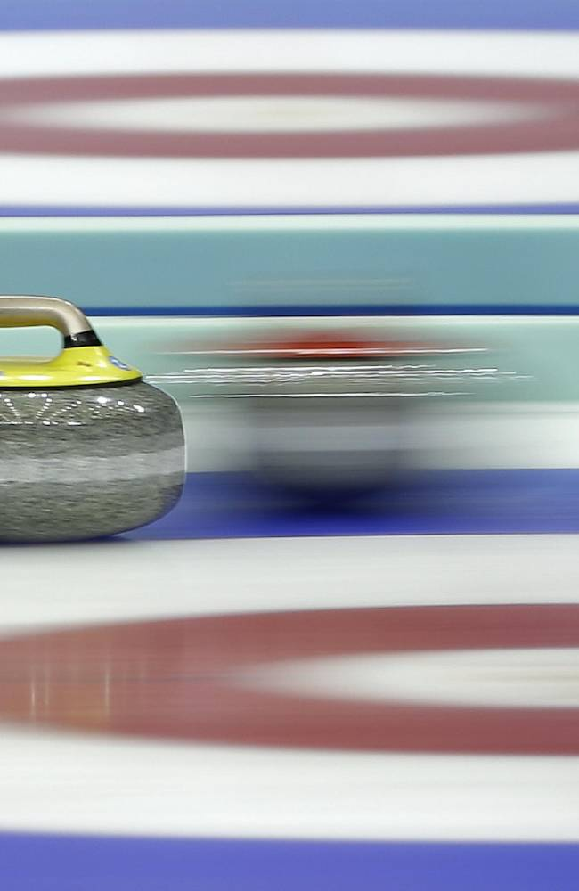 A stone passes another during a semi-final match between Canada and Sweden at the 2014 World Men's Curling Championship held at the Capital Gymnasium in Beijing, China, Saturday, April 5, 2014