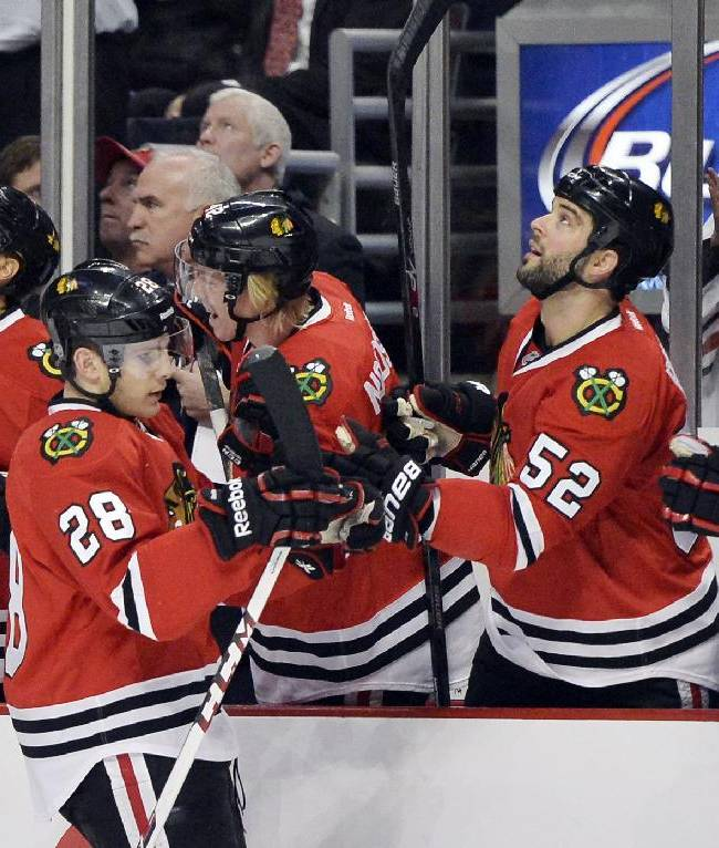 Chicago Blackhawks right wing Ben Smith, left, is congratulated by teammates Brandon Bollig, second from right, and Sheldon Brookbank, right, after Smith scored a goal during the first period of an NHL hockey game against the Anaheim Ducks, Friday, Dec. 6, 2013, in Chicago