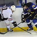 St. Louis Blues' T.J. Oshie (74) and Chicago Blackhawks' Patrick Sharp (10) reach for the puck during the second period in Game 2 of a first-round NHL hockey playoff series on Saturday, April 19, 2014, in St. Louis The Associated Press