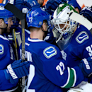 Vancouver Canucks goalie Eddie Lack, right, of Sweden, is congratulated on his shutout by teammates Daniel Sedin, center, of Sweden, and Jeremy Welsh after the Canucks defeated the Carolina Hurricanes 2-0, in an NHL hockey game, in Vancouver, British Colu