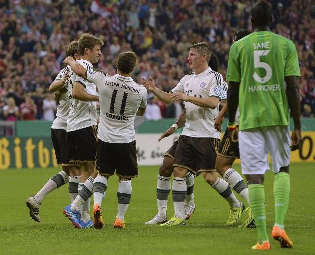 Munich's players celebrate after scoring during the German soccer cup second round match between FC Bayern Munich and Hannover 96, in Munich, southern Germany, Wednesday, Sept. 25, 2013