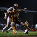 West Ham's Joe Cole, back, competes for the ball with Hull City's Shane Long during the English Premier League soccer match between West Ham and Hull City at Upton Park stadium in London, Wednesday, March 26, 2014