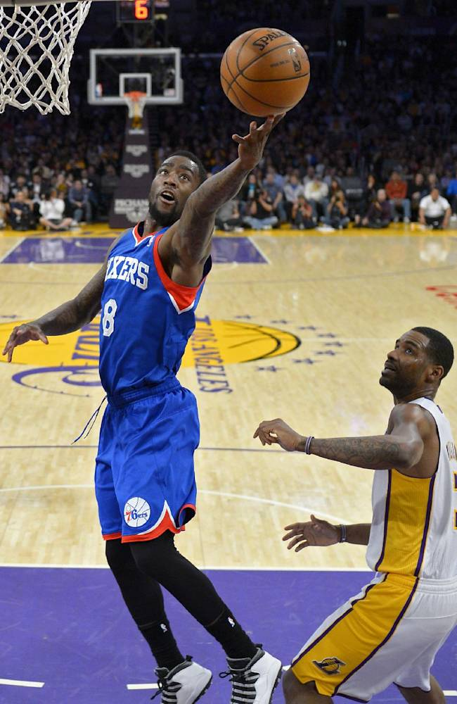 Philadelphia 76ers guard Tony Wroten, left, puts up a shot as Los Angeles Lakers forward Shawne Williams defends during the first half of an NBA basketball game, Sunday, Dec. 29, 2013, in Los Angeles