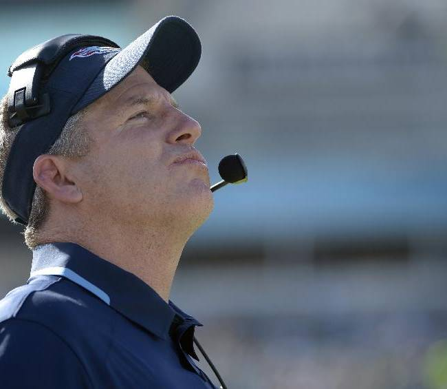 In htis Dec. 22, 2013, file photo, Tennessee Titans head coach Mike Munchak watches the stadium video monitor during the first half of an NFL football game against the Jacksonville Jaguars in Jacksonville, Fla.  A person familiar with the decision say Titans President Tommy Smith has fired  Munchak after three seasons as his head coach and 31 years combined with this franchise as a player and coach. The person spoke to The Associated Press on Saturday, Jan. 4, 2014, on the condition of anonymity because the Titans have not made an official announcement