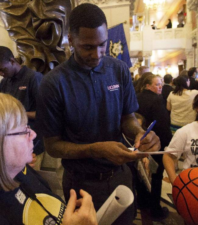 Connecticut's NCAA college basketball player Phillip Nolan, center, signs an autograph for a fan during Husky Day at the Connecticut Capitol on Wednesday, April 30, 2014, in Hartford, Conn