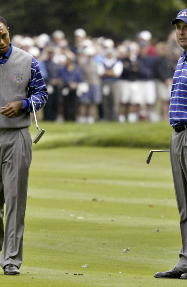 FILE - In this Friday, Sept. 17, 2004 file photo, Tiger Woods, left, and Phil Mickelson, of the United States team, walk up on the 17th green in their four-ball match against Europeans Colin Montgomerie and Padraig Harrington, during the 35th Ryder Cup golf competition, at Oakland Hills Country Club in Bloomfield Township, Mich. US captain Hal Sutton had hoped the Woods/Mickelson partnership would deliver for his team despite their apparent fractured relationship. In the event, they lost both the matches they played together as Europe romped home to reclaim the Ryder Cup by a 18 1/2 - 9 1/2 scoreline. (AP Photo/Morry Gash, File)