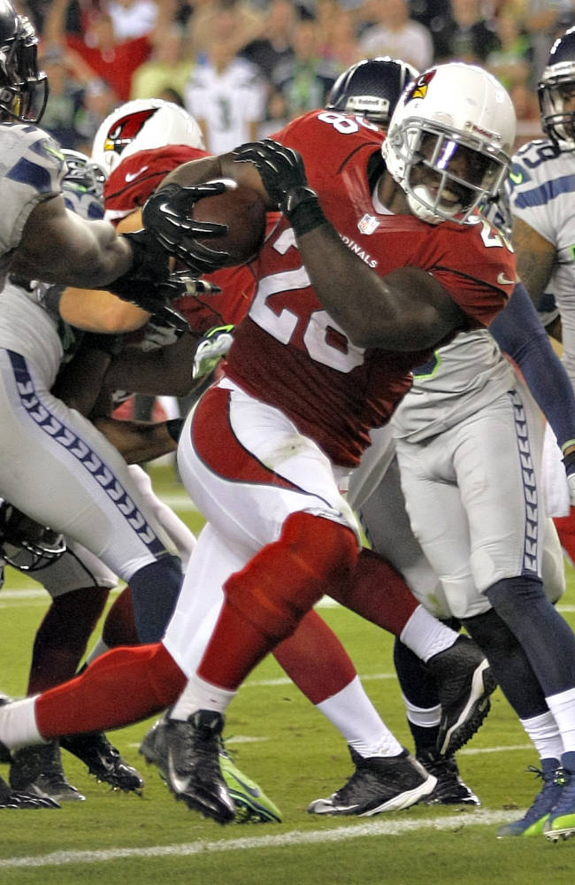 Arizona Cardinals running back Rashard Mendenhall (28) scores a touchdown as Seattle Seahawks outside linebacker Bruce Irvin (51) defends during the first half of an NFL football game, Thursday, Oct. 17, 2013, in Glendale, Ariz